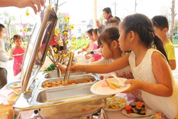 Bé lấy các món ăn được giữ nóng trong nồi hâm buffet
